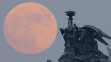 Super-sized: The full moon rises behind statues of angels fixed at the St Isaak's Cathedral in St Petersburg, Russia last night.