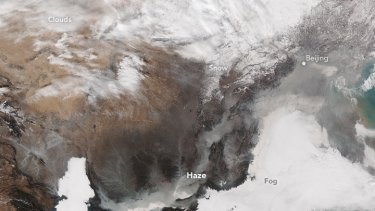 A NASA satellite photo shows smog over Beijing on November 30, 2015. The brightest areas are clouds or fog, tinged with yellow or grey because of air pollution.
