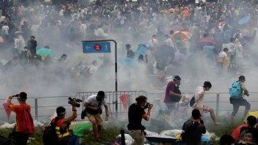 Warning shot: Protestors flee tear gas near Hong Kong's government headquarters.