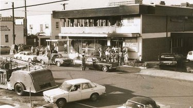 Fifteen people dead: Onlookers mill outside the shell of Brisbane's burnt-out Whiskey Au Go Go in March 1973.