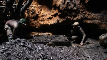 """""""I have never seen a school"""": Gayasuddin, with a colleague, emerges from the rat-hole mine with a full cartload of coal."""