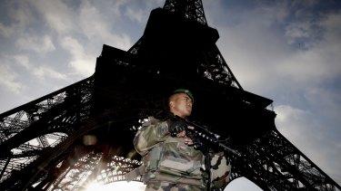 Armed military patrol the Eiffel Tower.