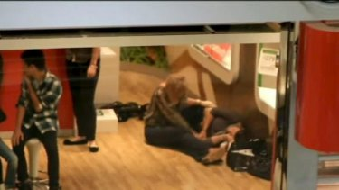 A woman is comforted after yesterday's shooting in the Robina Town Centre.