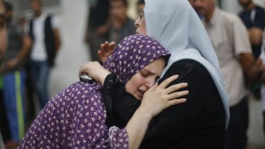 The mother of two boys killed by an Israeli air strike grieves during their funeral outside a hospital morgue.