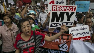 Pro-government red shirts protesters march as violence escalates before the controversial elections Sunday in Bangkok.