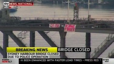 Major delays ... a man has been arrested after unfurling these two banners on the Harbour Bridge.