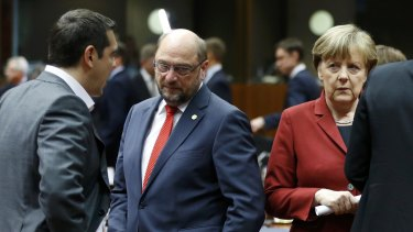 Greek Prime Minister Alexis Tsipras talks to European Parliament President Martin Schulz and Germany's Chancellor Angela Merkel on Thursday in Brussels.