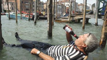 Drastic measures: A gondolier deals with a 32-degree day in Venice this week, drinking beer in a chair submerged in the Grand Canal.