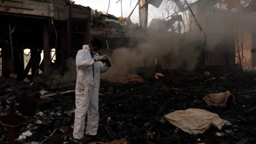 A man takes photos of the damage caused by the reception hall airstrike.