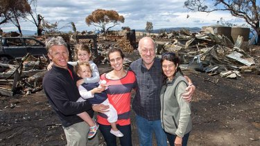 The Holmes family, who had to shelter underneath a jetty to escape the recent bushfire on Tasmania's east coast,  at their property near Dunalley today.