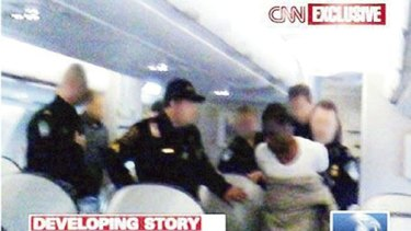 CNN Video still of terror suspect Umar Farouk Abdulmutallab being restrained by passengers and officials.