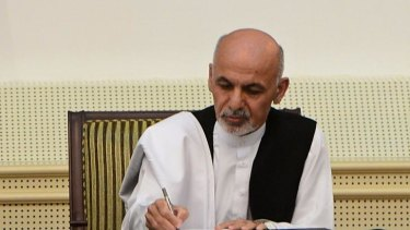 Afghan president Ashraf Ghani Ahmadzai signs a power-sharing agreement with unseen rival Abdullah Abdullah at the Presidential Palace in Kabul on September 21, 2014.