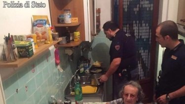 One officer chats to the elderly couple as another washes up.