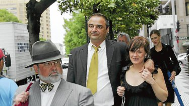 Ali Alkan (right, at centre) leaves court on Friday.