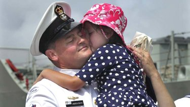 Emotional: Maddie, 5, hugs her father Petty Officer Andrew Booth.
