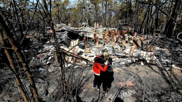 NSW towns count their bushfire losses: Catherine Hubbard and daughter Amy stand in front of the burnt ruins of their home in Winmalee, in the Blue Mountains.