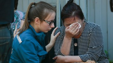 An emergency worker comforts a woman outside the burnt building.