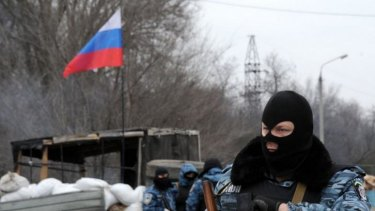 Armed masked men stand at their checkpoint under a Russian flag on a highway that connects the Crimean peninsula to mainland Ukraine.