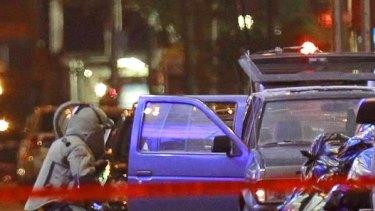 Police examine the car bomb.