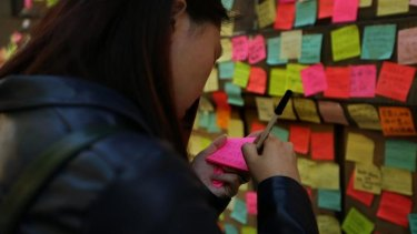A woman from Hong Kong, whose friends are part of the protest, writes a message of support to post on the wall of Hong Kong House