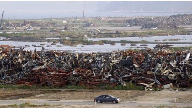 A car drives past a pile of wrecked vehicles, destroyed by the March 11th earthquake and tsunami.