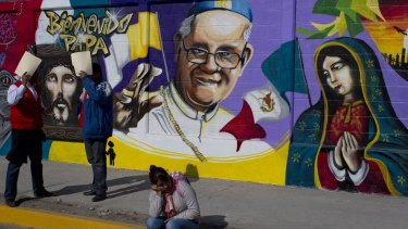 A woman sits in front of a mural of Pope Francis in Mexico City, a city the Pope is visiting this month.