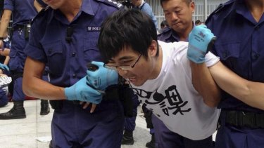 Alex Chow Yong-kang, general secretary of the Hong Kong Federation of Students, is taken away by police during protests.