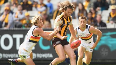 MELBOURNE, AUSTRALIA - APRIL 01: Ty Vickery of the Hawks kicks whilst being tackled Daniel Talia of the Crows during the round two AFL match between the Hawthorn Hawks and the Adelaide Crows at Melbourne Cricket Ground on April 1, 2017 in Melbourne, Australia. (Photo by Quinn Rooney/Getty Images)