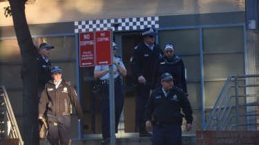 Police at Merrylands Police Station after Thursday night's attack.