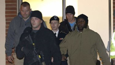 Army Pfc. Bradley Manning, center, is escorted out of a courthouse in Fort Meade, Md., after attending a pretrial hearing.