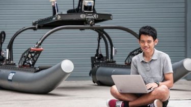 QUT student Amit Chongbang with the robot boat.