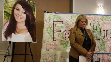 Sheila Pott, mother of Audrie Pott, stands by a photograph of her daughter  during a news conference after the arrest of three boys for sexual assault.