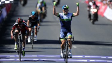 Simon Gerrans raises his arms in triumph as he finishes ahead of Cadel Evans and Richie Porte.