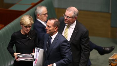 Prime Minister Tony Abbott departs question time with Julie Bishop and Scott Morrison while Malcolm Turnbull remains on the frontbench.