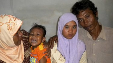 Wati with her father Yusuf, mother Yusniar and younger brother Aris at their home in Meulaboh, Aceh province, Indonesia.