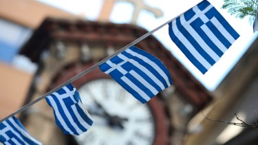 Greek national flag bunting hangs in front of a church in Athens on Thursday. Greek voters are split heading into a referendum European leaders said could plunge the country into economic darkness.