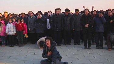 A woman cries near a statue of former North Korean leader Kim Il-sung.