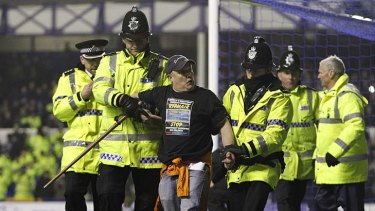 Protest ...  the man is taken away after handcuffing himself to the goalpost