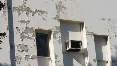 Paint peels off the outside walls of the Waltons building.