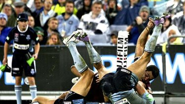 Hopes turned upside down . . . NSW take out Greg Inglis during last night's State of Origin opening game in Sydney.