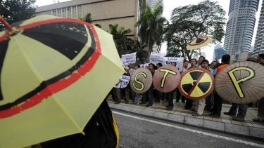 Activists hold umbrellas with anti-radiation symbols on them during a demonstration against the proposed rare earth plant, last year.