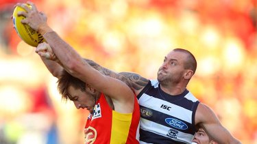 Holding firm: Gold Coast's Charlie Dixon marks strongly, despite Cat Josh Hunt's attempt to spoil.