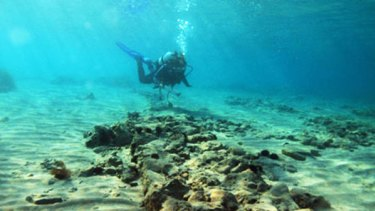 Planned town dating back about 5000 years  ... a diver explorers the sunken settlement.