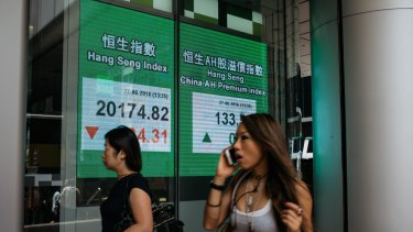 Pedestrians walk past an electronic screen displaying the Hang Seng Index, left, in the Central district of Hong Kong.