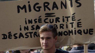 "Far-right: A man holds a banner at a protest in Calais on Sunday that reads ""Migrants equal insecurity, unhealthiness and economic disaster""."