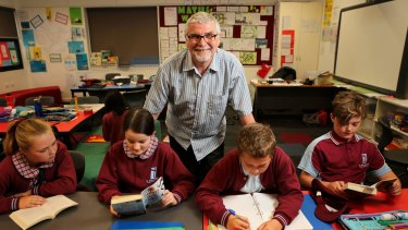 Switched: Michael Higgins, with some of his grade 5 students. The former engineer went into teaching at an age when some are considering retirement and loves the classroom.