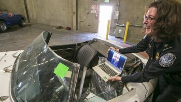 US Customs and Border Protection, public affairs liaison chief, Lee Ann Harty, shows a 1967 Jaguar XKE convertible that was stolen 46 years ago to the original owner, car collector Ivan Schneider, via video conference.