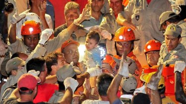 Where there's life ... firefighters hold Nicolas Barreto, who survived 15 hours trapped in a buried house.