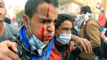 An injured Egyptian protester ... is helped away during clashes.