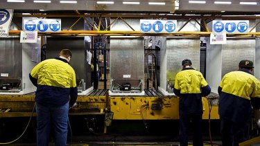 An employee of Electrolux adds components to a fridge at the Electrolux Factory in Orange, NSW.